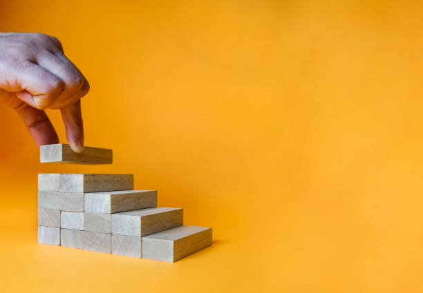 Hand arranging wood block stacking as step stair. Ladder career path concept for business growth success process. stock photo