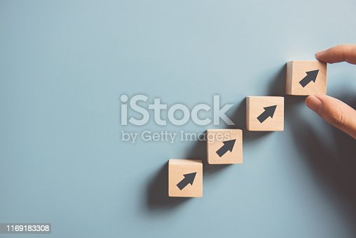 istock Hand arranging wood block stacking as step stair on paper pink background. Business concept growth success process, copy space. 1169183308