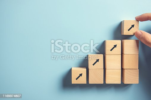 istock Hand arranging wood block stacking as step stair on paper pink background. Business concept growth success process, copy space. 1169974807