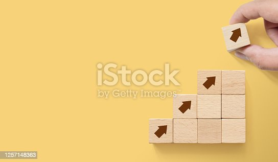 Hand arranging wood block stacking as step stair on paper yellow background with copy space. Ladder career path concept for business growth success process