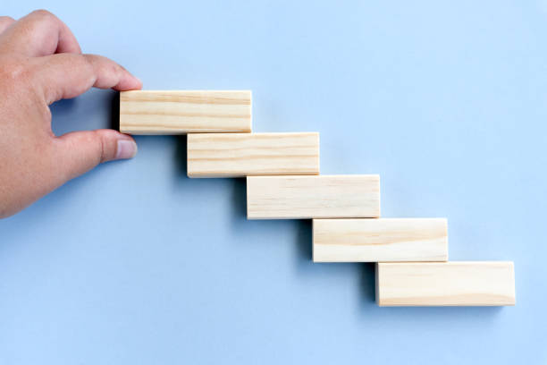Hand arranging wood block stacking as step stair. stock photo
