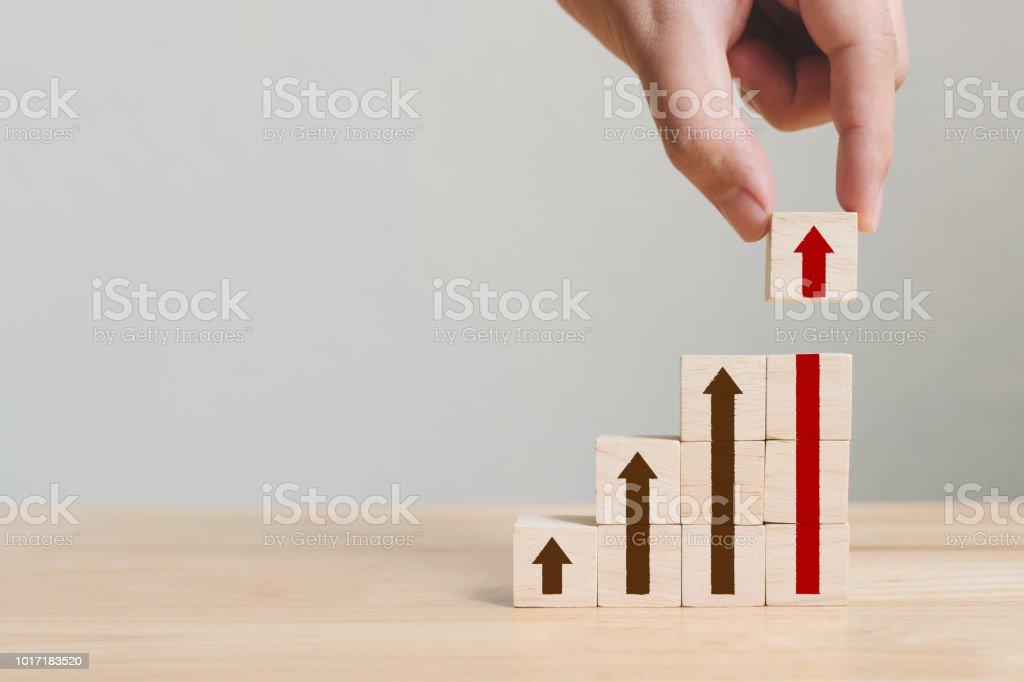 Bloque de madera arreglo apilar como escalera de paso con la flecha para arriba de la mano. Concepto de trayectoria de carrera escalera para proceso de éxito de crecimiento de negocio foto de stock libre de derechos