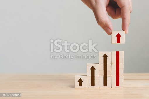istock Hand arranging wood block stacking as step stair with arrow up. Ladder career path concept for business growth success process 1017183520