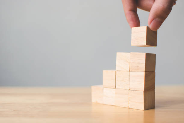 hand schikken hout blok stapelen op top met houten tafel. businessconcept voor succes groeiproces - hand constructing industry stockfoto's en -beelden