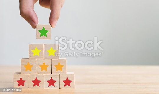 1133580311 istock photo Hand arranging wood block stacking with icon five star symbol. Rating customer service satisfaction experience concept 1042157166