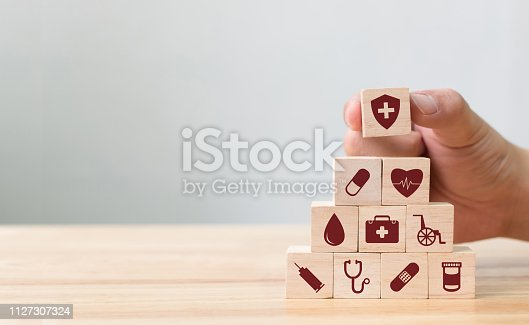 917079152istockphoto Hand arranging wood block stacking with icon healthcare medical, Insurance for your health concept 1127307324