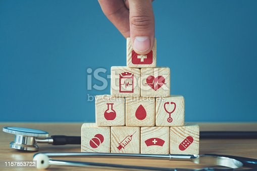 1029077176istockphoto Hand arranging wood block stacking with icon healthcare medical, Insurance for your health concept 1157853722