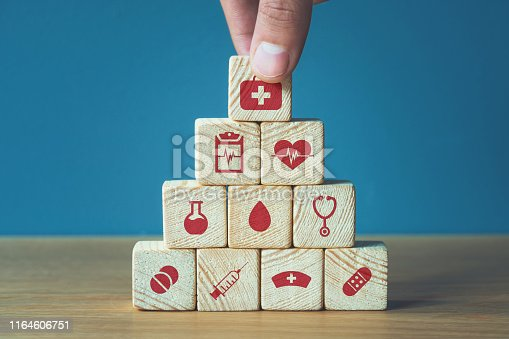 1029077176istockphoto Hand arranging wood block stacking with icon healthcare medical, Insurance for your health concept 1164606751