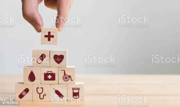 Hand arranging wood block stacking with icon healthcare medical for picture id917079152?b=1&k=6&m=917079152&s=612x612&h=u8lskfd7waoty1xc903dxdbd1ge4bg6mxm2fru23gc4=
