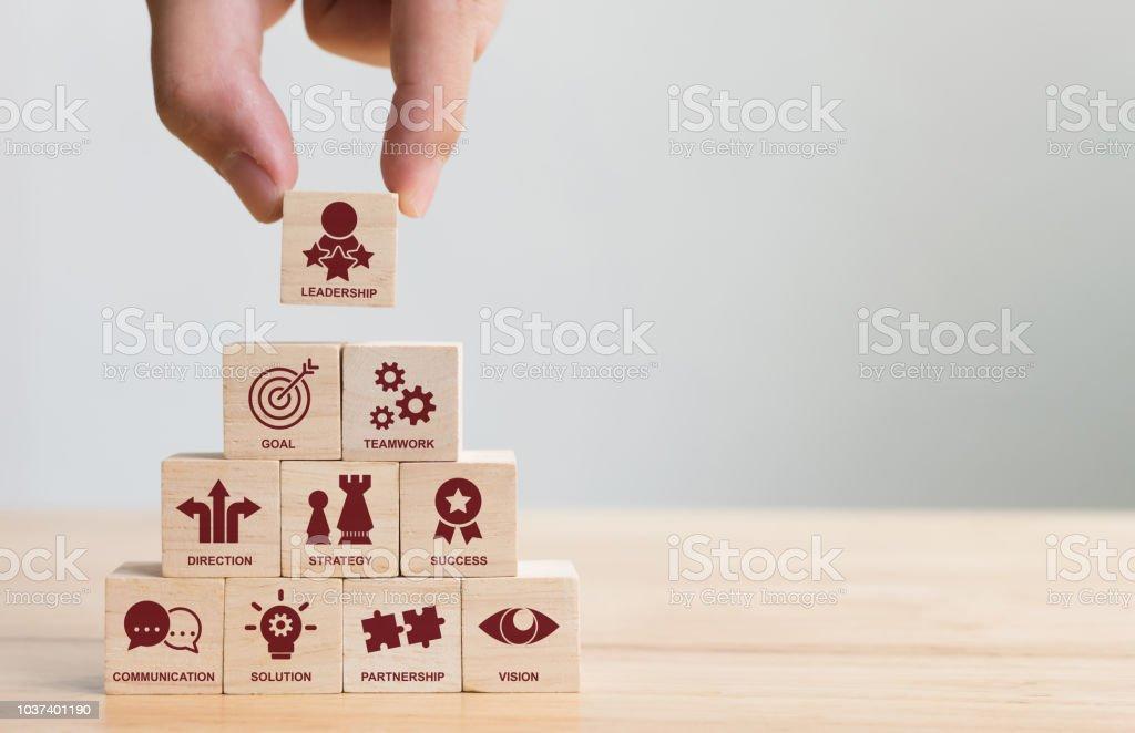 Hand, die Vermittlung von Holz-Block Stapeln mit Symbol Führer Unternehmen. Wichtige Erfolgsfaktoren für Führung Elemente Konzept – Foto