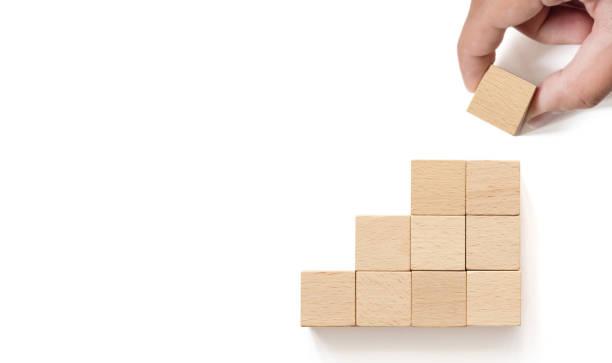 mão que arranja o bloco de madeira que empilhe como a escada da etapa no fundo do whith. conceito do negócio para o processo do sucesso do crescimento. copie o espaço - bloco - fotografias e filmes do acervo