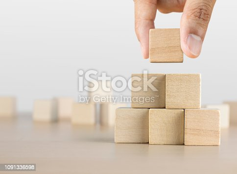 istock Hand arranging wooden blocks stacking as a pyramid staircase on white background. Success, growth, win, victory, development or top ranking concept. 1091336598