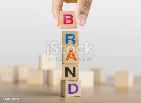 Hand arranging wooden blocks with the word BRAND. Brand building concept.