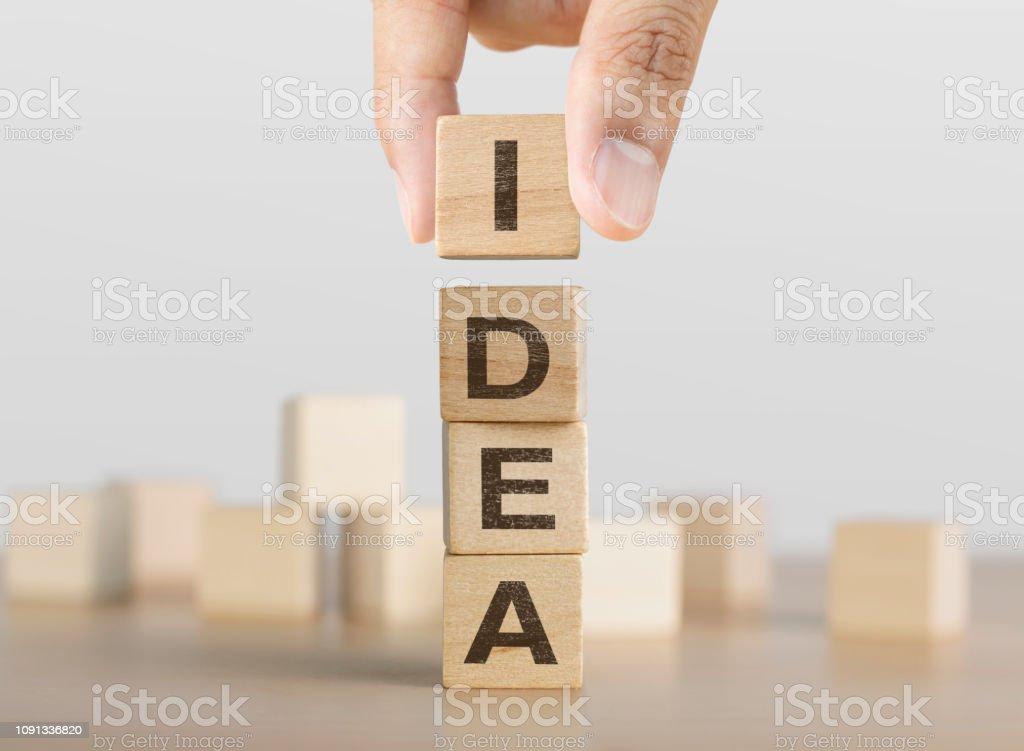 Hand arranging wooden blocks with the word IDEA. Idea, Creative,...