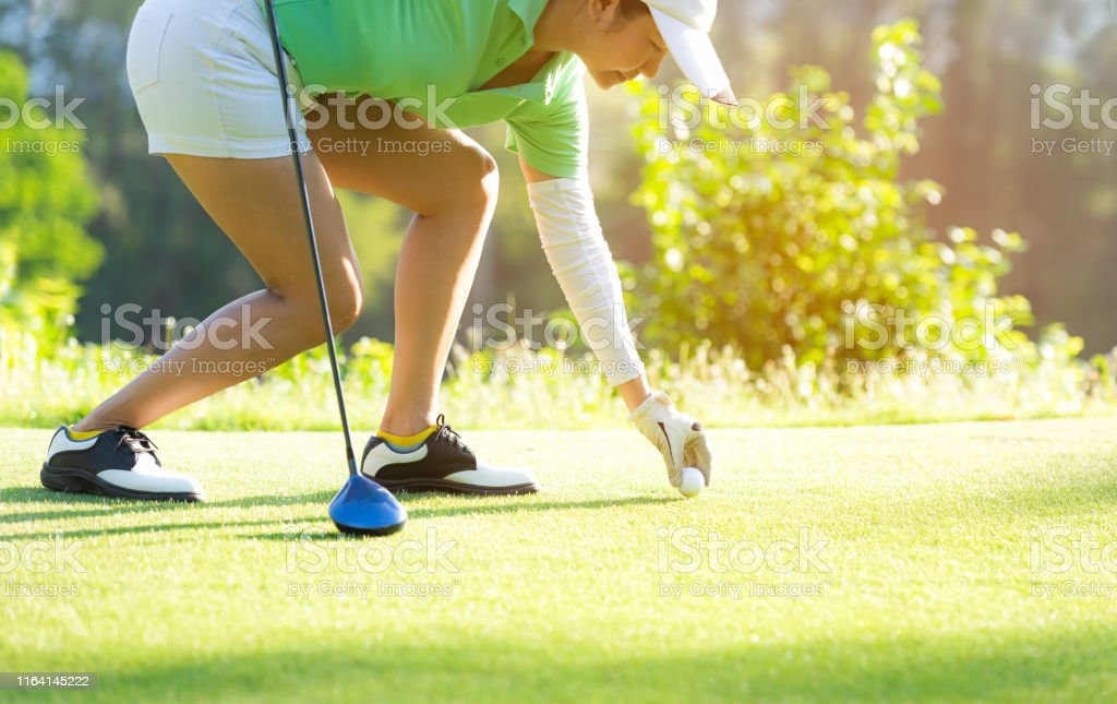 Hand asian sporty woman putting golf ball on tee with club in golf...