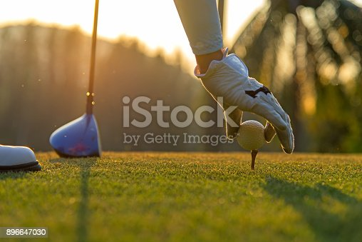 Hand asian woman putting golf ball on tee with club in golf course on evening and sunset time a for healthy sport.  Lifestyle Concept