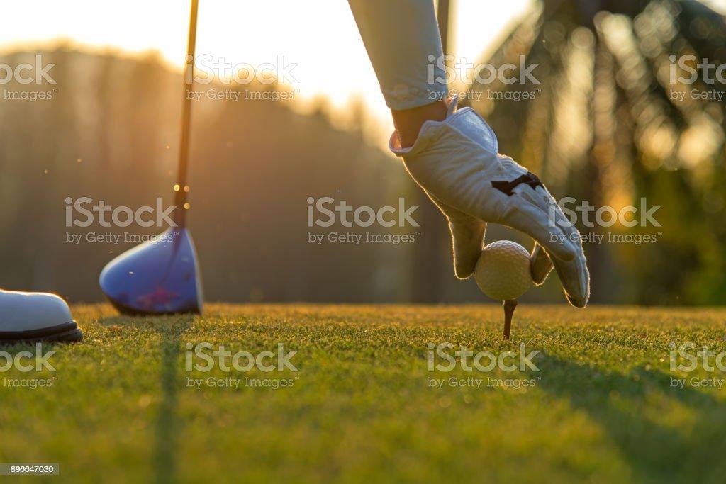 Mujer asiática mano colocarle la pelota de golf tee con club de golf del tiempo de la tarde y al atardecer un deporte saludable.  Concepto de estilo de vida - foto de stock