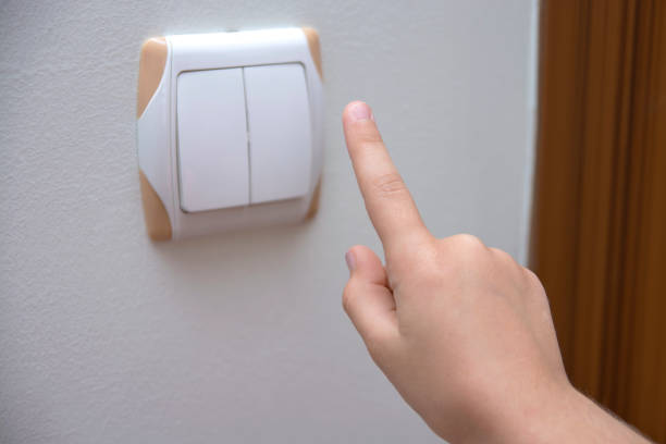 Hand At Turning Off Light Switch stock photo