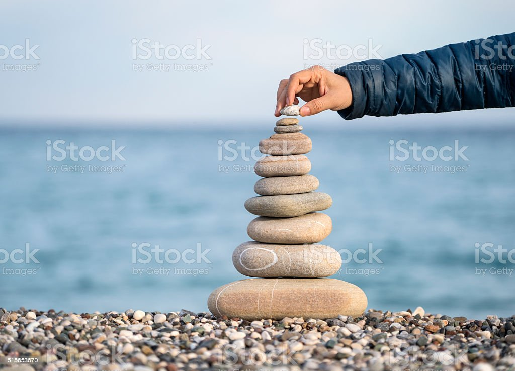 Hand balancing stack of stones on beach stock photo