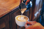 Hand barista pouring milk on coffee latte flower shape in white cup