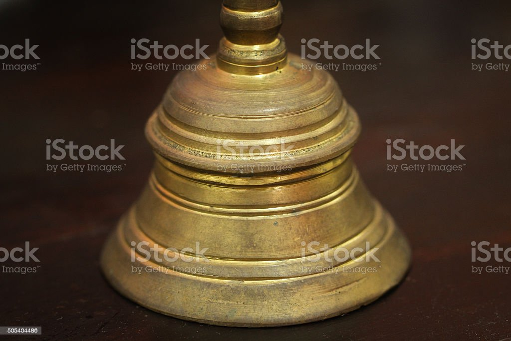 hand bell on dark brown wood table stock photo