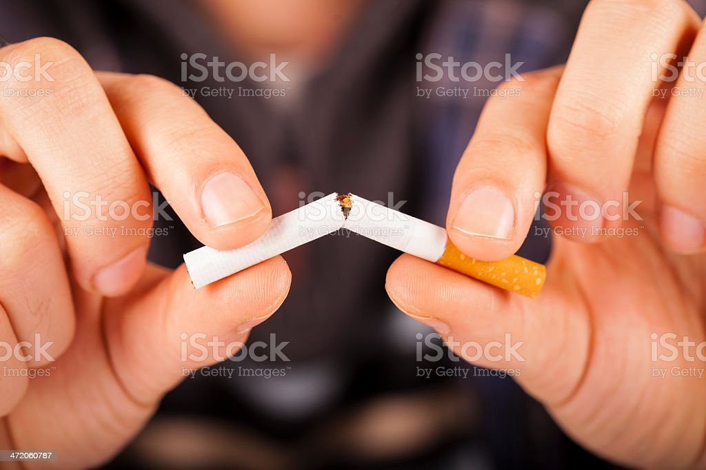 Hand breaking a cigarette in half stock photo