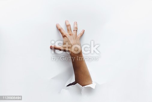 istock A hand breaks through the obstacle and tries to grab something greedily. Secret desire. Stealing. 1125935494