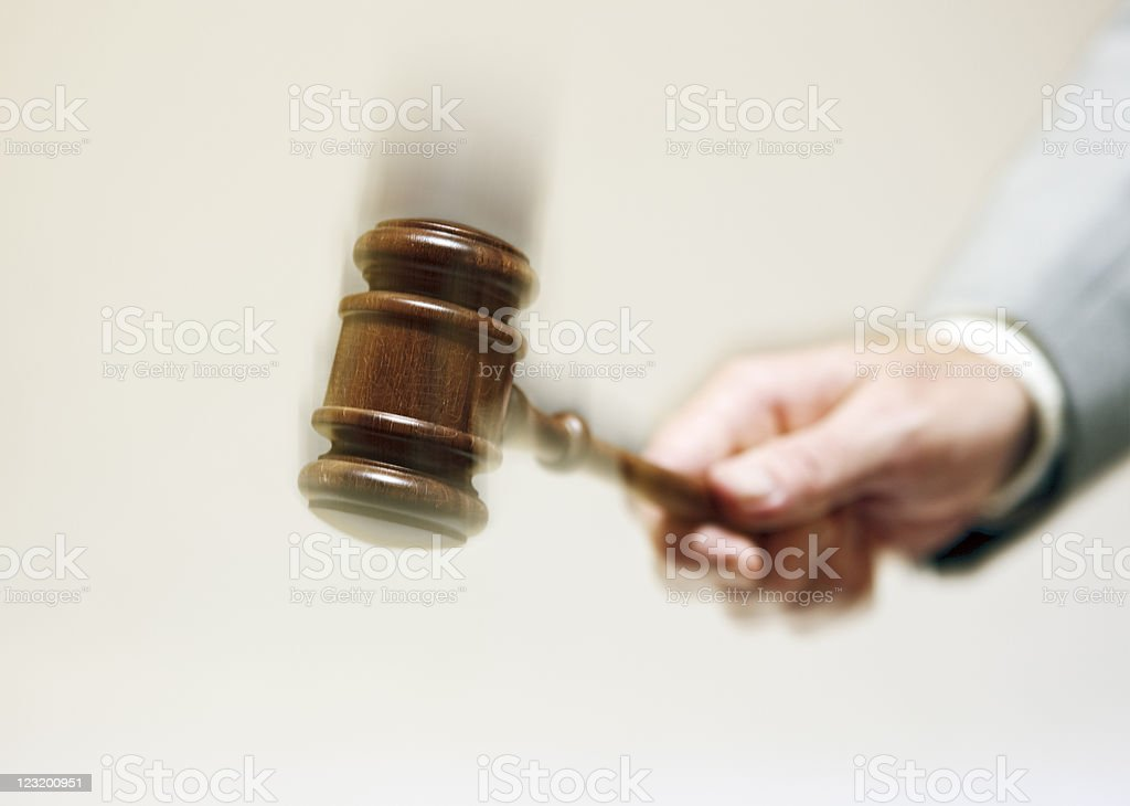 Hand bringing down gavel with exaggerated motion blur royalty-free stock photo