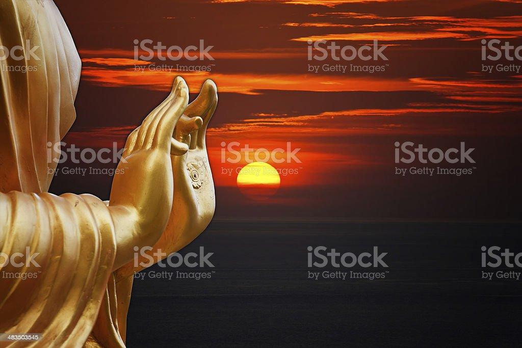 hand Buddha statue with sunset sky background stock photo