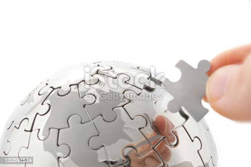 638813890istockphoto hand building puzzle globe on white 120591524