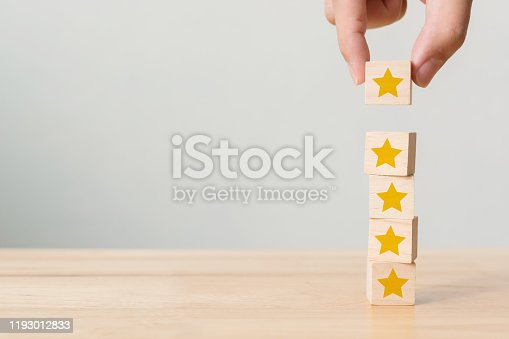 1133580311 istock photo Hand building wood block cube stacking on top with five star shape. The best excellent business services rating customer experience concept 1193012833