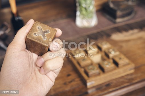Hand business man hold OX (tic tac toe) wood board game using as background business direction, planning concept. vintage tone.