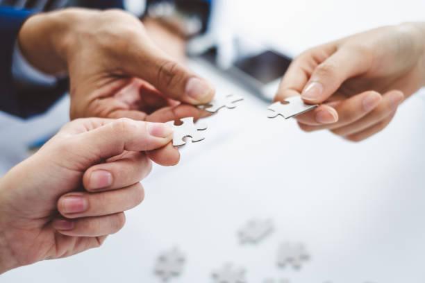 hand-business-mann hält puzzle für verbindung teamarbeit zusammen konzept - puzzleteil stock-fotos und bilder