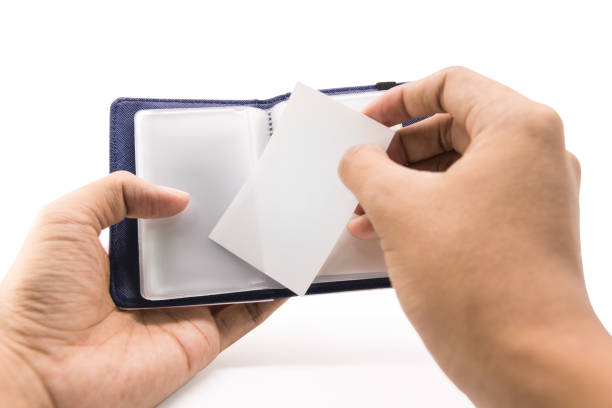 A hand businessman put white card or name contact into blue leather wallet on isolated background with clipping path. stock photo