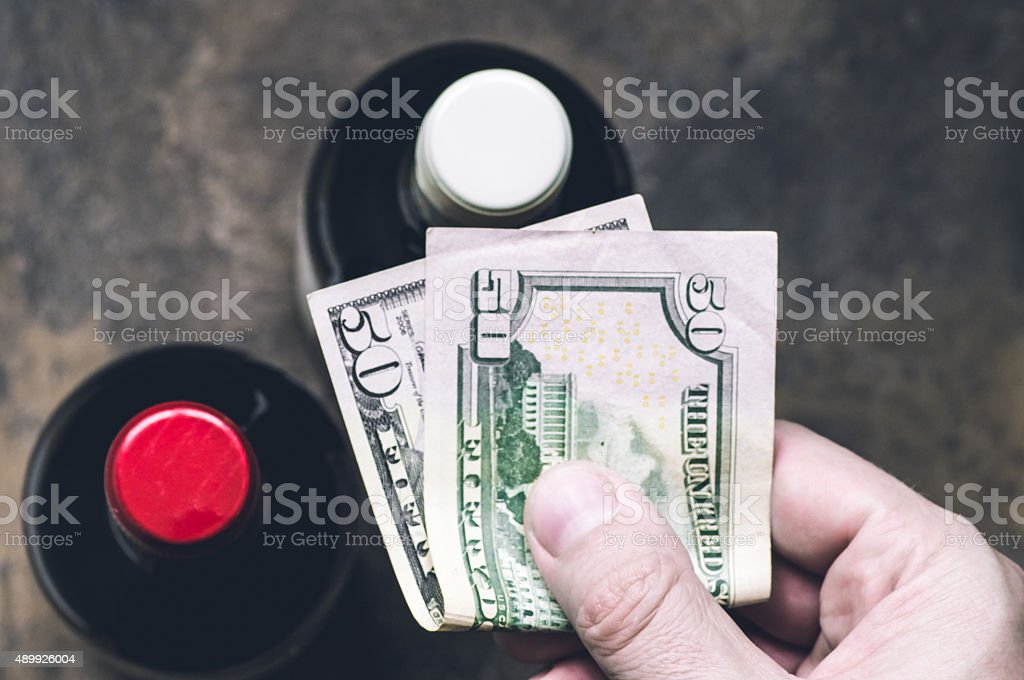 Hand buyer with dollars in liquor store stock photo