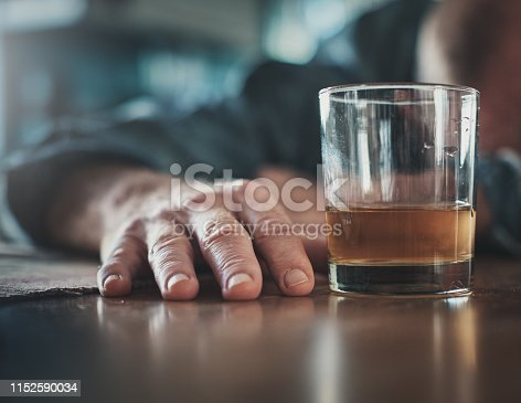 A man seems to have passed out or be sleeping, his head on a table, his hand near a glass of an alcoholic drink.