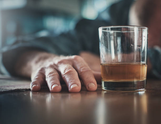Hand by glass of liquor, man's head on table stock photo
