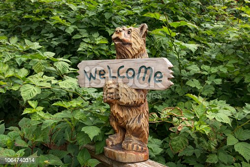 Small carved wooden bear holding a welcome sign