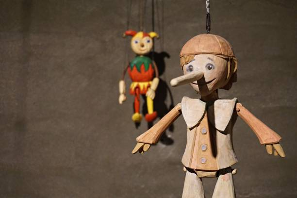 Hand carved wooden string puppets. A wooden doll hanging on a wall. puppet stock pictures, royalty-free photos & images