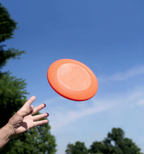 Hand catching orange frisbee against blue sky background A single hand is reaching up to catch and orange frisbee against a blue sky.  Here are some other frisbee photos.  plastic disc stock pictures, royalty-free photos & images