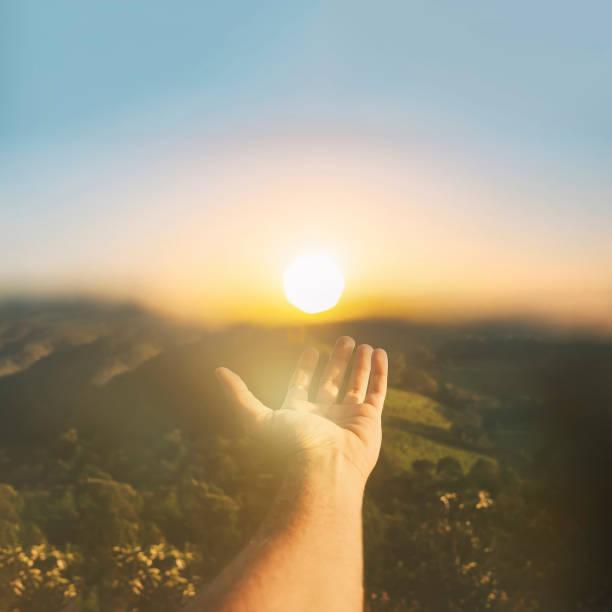 Handfängende Sonne am Sonnenuntergang. Das Konzept von Spiritualität Wohlbefinden und positive Energie – Foto
