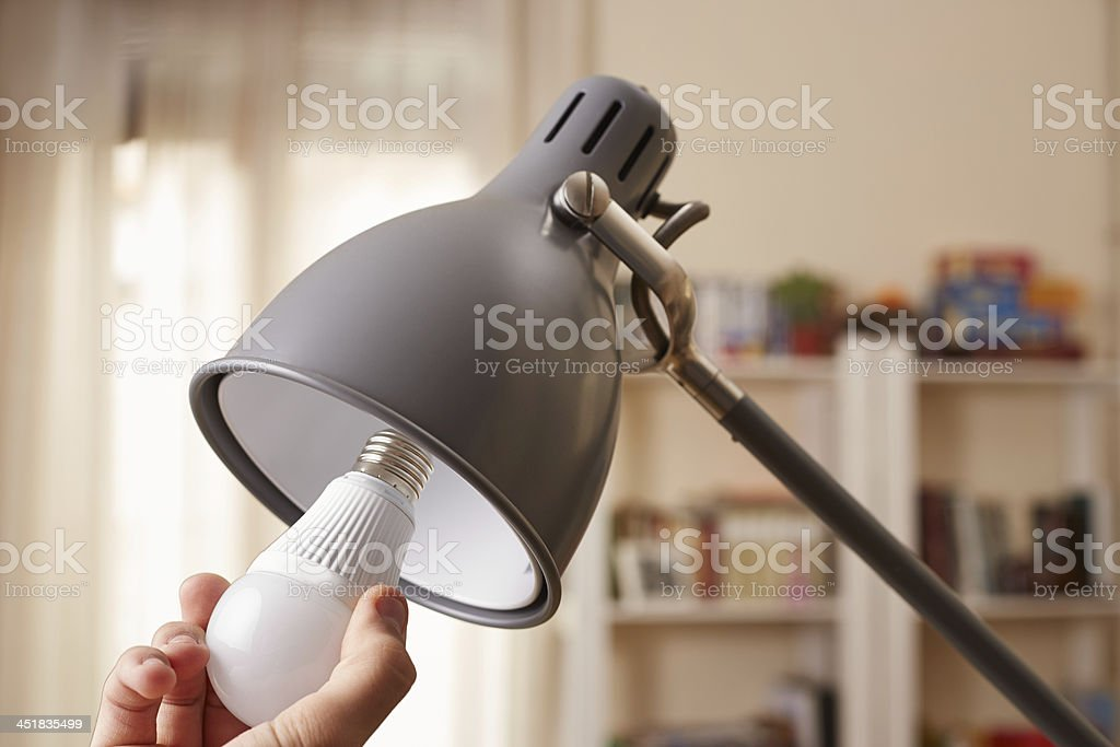 Hand changing a regular light bulb for LED stock photo