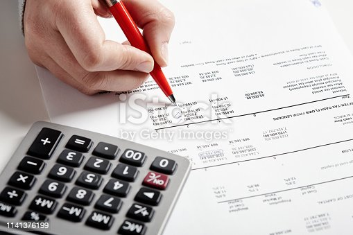 A hand holding a pen checks off items on a financial document, a calculator standing by.