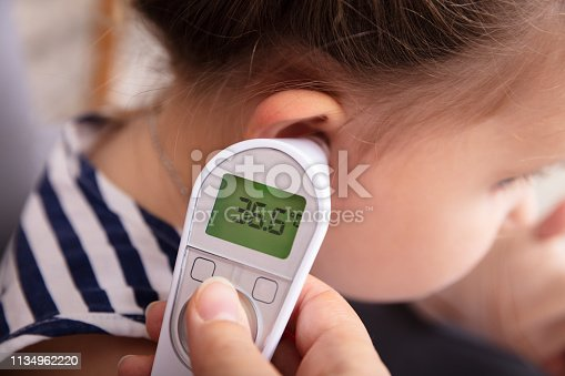 Close-up Of Hand Checking Girl's Ear With Digital Thermometer