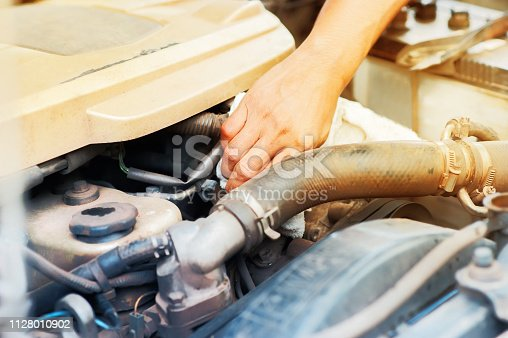 istock Hand checking on car radiator of overheating 1128010902