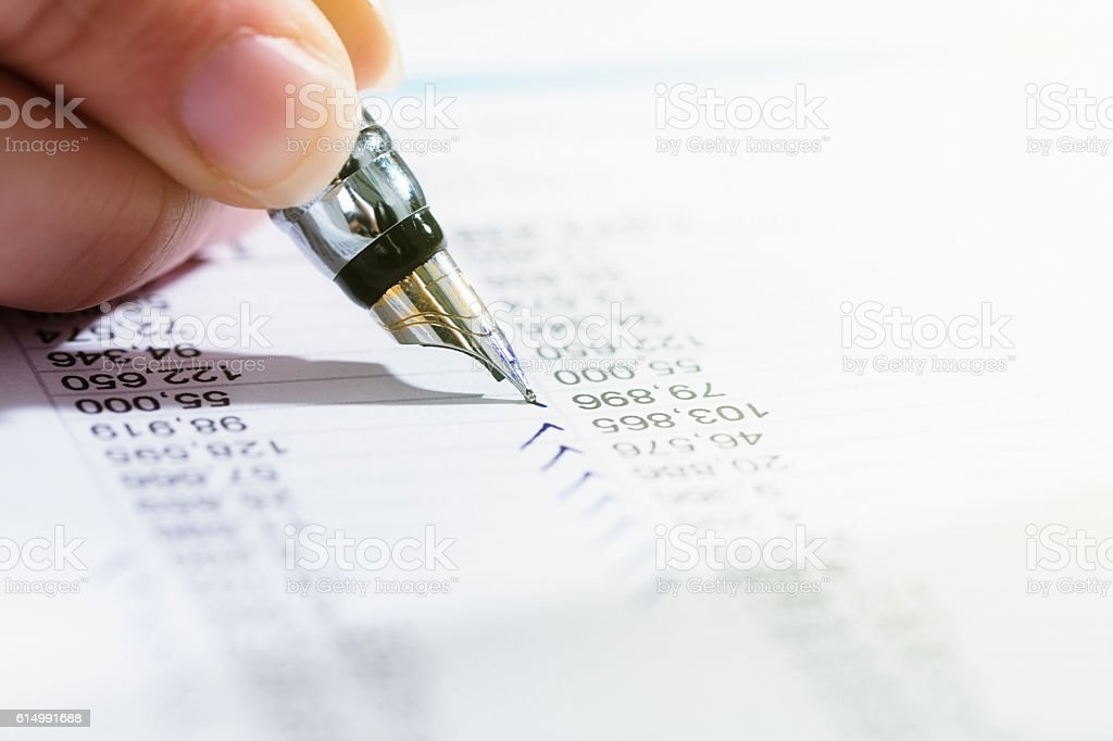 Hand checks financial document with fountain pen stock photo