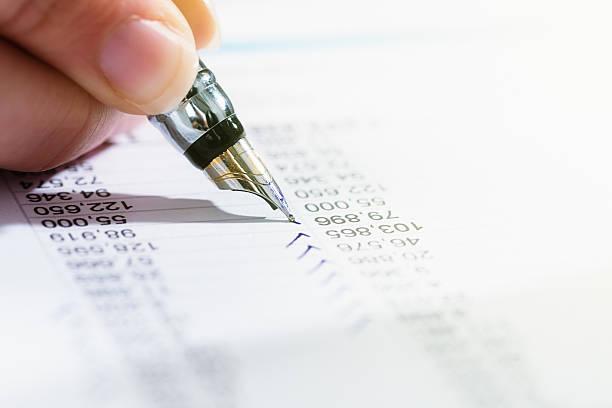 Hand checks financial document with fountain pen - foto de stock