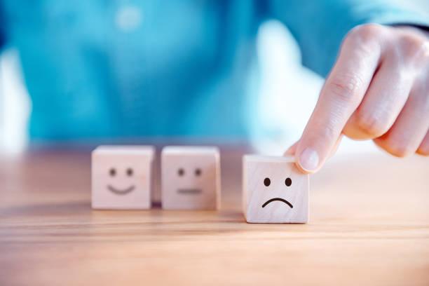 Hand wählen Sie traurige Gesicht-Ikone auf Holzwürfel, Service-Rating, Zufriedenheit Konzept. – Foto