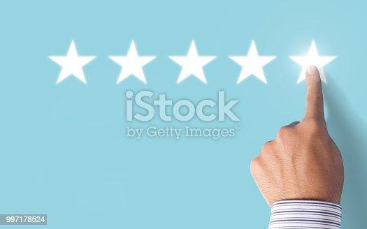 istock Hand choosing 5 stars rating on blue background - Positive feedback 997178524