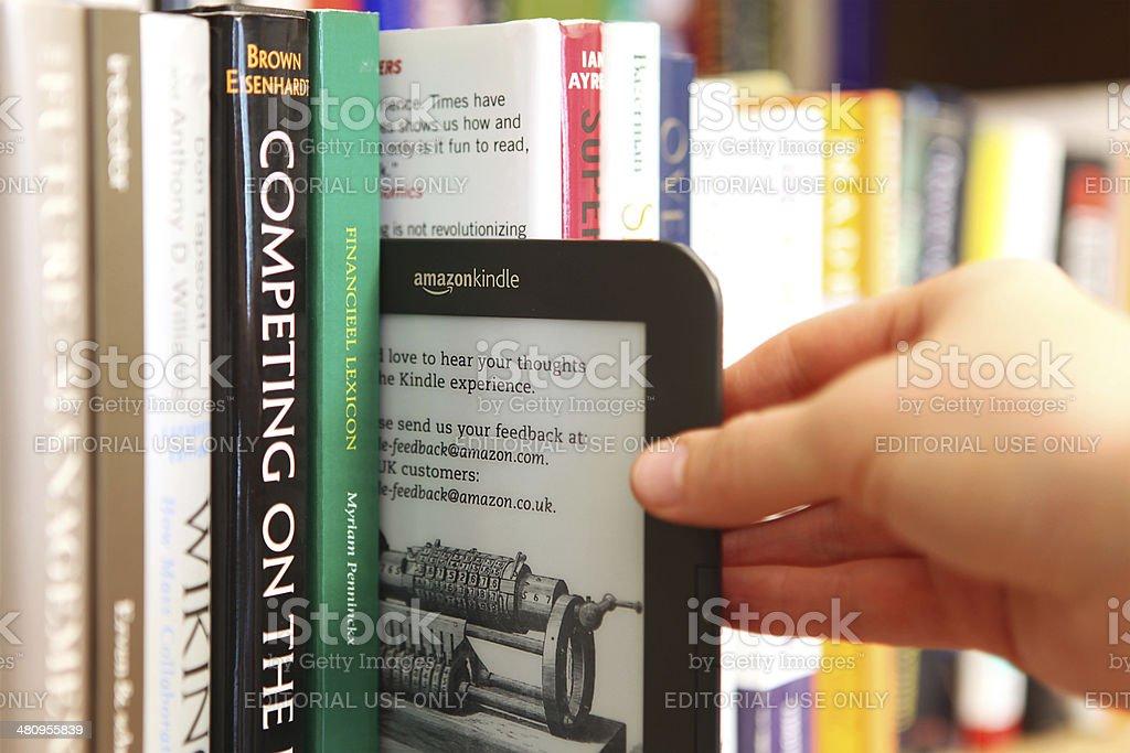 Hand Choosing A Kindle Ebook Vs Paper Book From Bookshelf